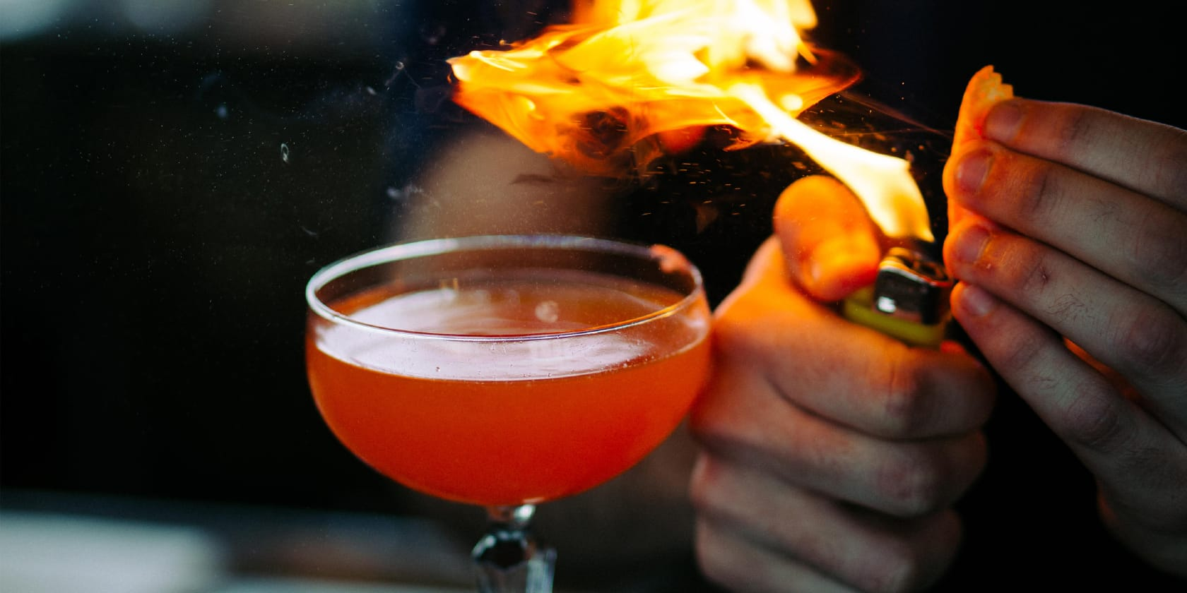 A bartender lights orange spritz over a cocktail.