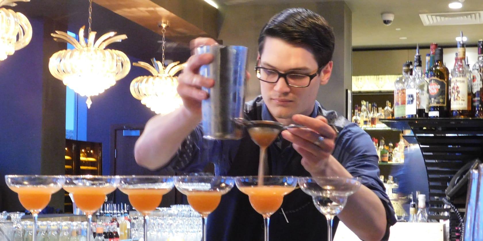 Bartender pouring cocktails.